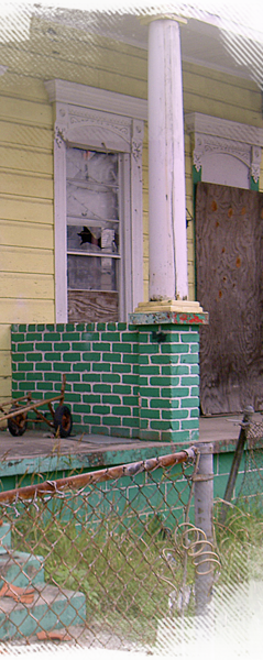 A yellow and green home is still boarded and vacant more than a year after Katrina 239x600